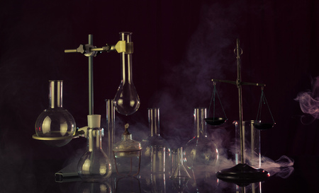 Mysterious laboratory. Chemical glassware and a tripod, laboratory scales. All the highlighted smoke 版權商用圖片 - 124679746