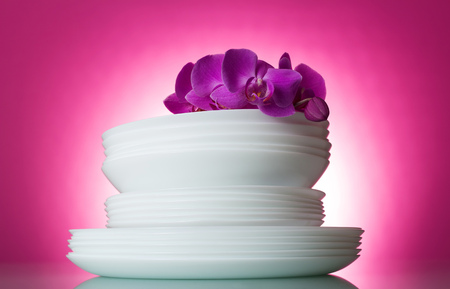 Clean washed white plates on a pink background and an orchid branch 版權商用圖片