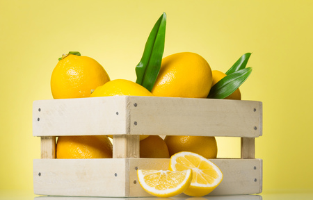 Fresh juicy lemons in a wooden box on yellow background