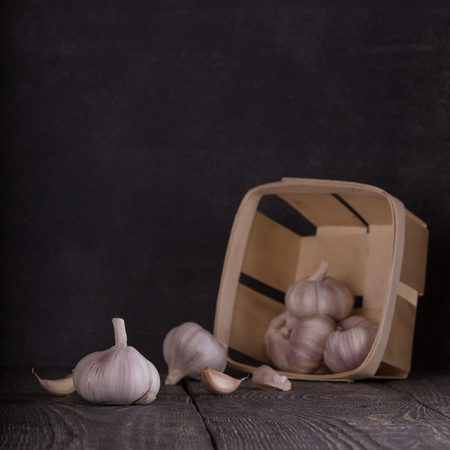 Scattered heads of garlic on a wooden table, a basket of garlic 版權商用圖片 - 124678668