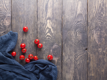 Small cherry tomatoes, blue napkin on wooden background 版權商用圖片 - 124678671