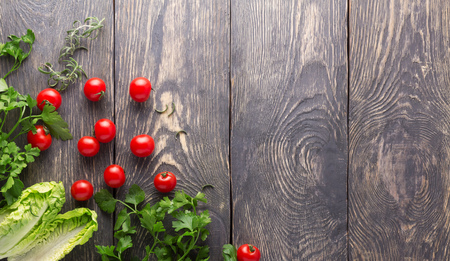 Cherry tomatoes, fresh parsley and a salad on dark boards