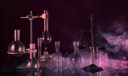 Magical laboratory. Chemical balance scales, a tripod with a variety of dishes on a dark background in the red smoke 版權商用圖片 - 124678689