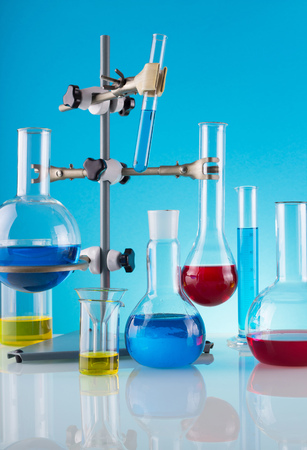 Biological laboratory. A tripod with a variety of chemical glass and colored liquids on a blue background 版權商用圖片