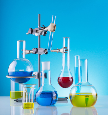 Biological laboratory. A tripod with a variety of chemical glass and colored liquids on a blue background 版權商用圖片 - 124678693