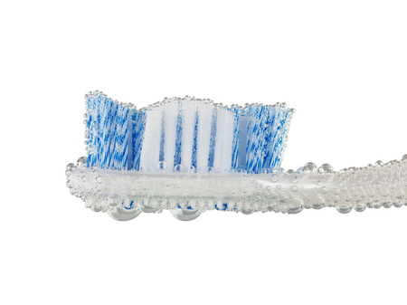 Toothbrush in bubbles of air isolated on white background. The concept of fresh breath.