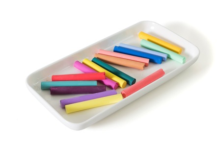 Colored chalk pastels in a beautiful white plate isolated on white background 版權商用圖片
