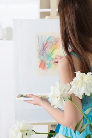 Girl artist painting an abstract painting with chalk pastels on white paper on an easel 版權商用圖片 - 124678733