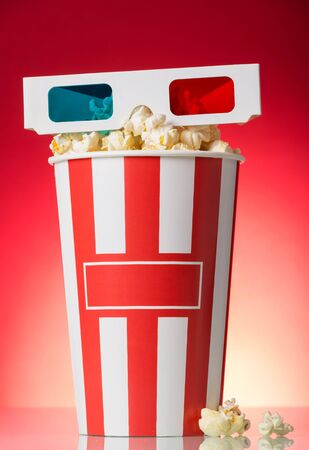 3D glasses, a box of popcorn and a few nearby on a bright red background.