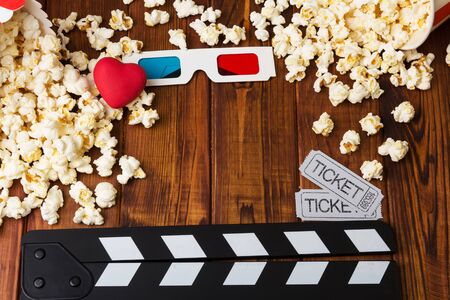 Lots of popcorn, 3D-glasses, red heart, movie tickets and movie clapper against the dark wood. Stock Photo