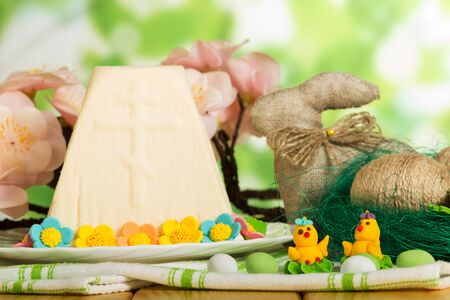 Easter cheese dessert on a plate decorated with flowers, Easter eggs wrapped with twine in the nest, Easter Bunny, toy chickens and candy on abstract green background.