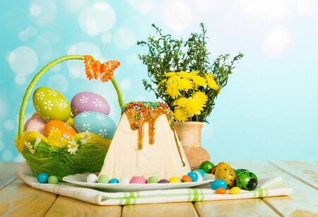 Traditional Easter cheesecake dessert watered glaze and decorated, different Easter eggs in a basket, vase with flowers and candy on an abstract blue background.