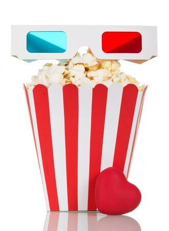 Striped box filled with popcorn, 3D glasses and a red heart isolated on white background.
