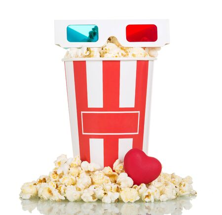 3D glasses, a striped box, filled with popcorn, popcorn around and red heart isolated on white background.