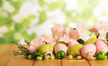 Various Easter eggs, candy, grass, branch with flowers on the abstract green background.