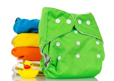 Bright modern environmentally friendly diapers and a rubber duckling isolated on white background.