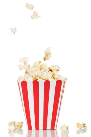 A falling popcorn in a large square box and beside her, isolated on white background. Standard-Bild