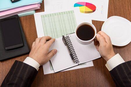 Desk, document folders, diary and coffee cup in hands of men Foto de archivo - 139415499