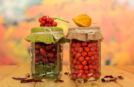 Banks with vitamin berries for future use, stand on wooden table Stockfoto