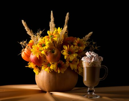 Original composition in the pumpkin, nearby cup of cappuccino with marshmallows, isolated on black background Stock Photo