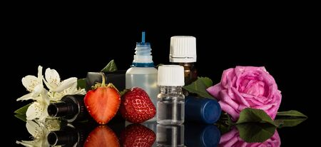 Set of fragrant liquids for smoking electronic cigarettes, berries and flowers isolated on black background