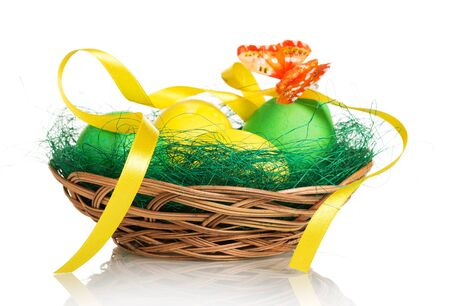 Colored Easter eggs in the basket and butterfly on a white background.