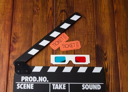 3D-glasses, movie tickets and movie clapper is against the dark wood.