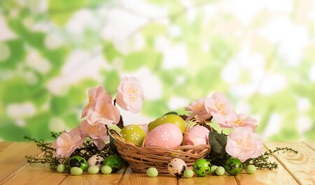 Various Easter eggs in a basket and near, candy, grass, branch with flowers on the abstract green background.