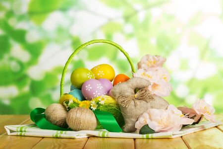 Colored Easter eggs in a basket next to the two intertwined cords, easter bunny, flowers and ribbons on the abstract green background.