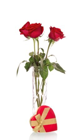 Scarlet roses in a glass vase and a heart shaped box isolated on white background