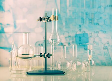 Laboratory conditions. Chemical scales, tripod with laboratory flasks and test tubes on blue