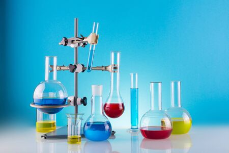 Biological laboratory. A tripod with a variety of chemical glass and colored liquids on a blue background Zdjęcie Seryjne