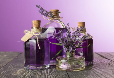 Bottles with decoction and lavender tincture with stoppers and label, flowers in vase, on wooden table