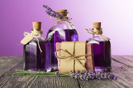 Bottles with lavender tincture closed cork, and piece of soap on old wooden table Banco de Imagens