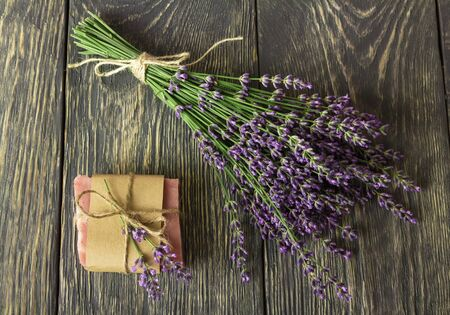 Handmade soap wrapped in paper, near on gray surface bunch of lavender Banco de Imagens