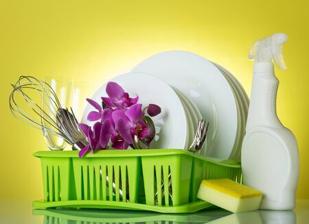 Clean plates and Cutlery on dryer, dish detergent and sponge, on bright yellow background