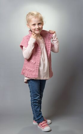 Charming blonde fashionista shows off her clothes, on gray background