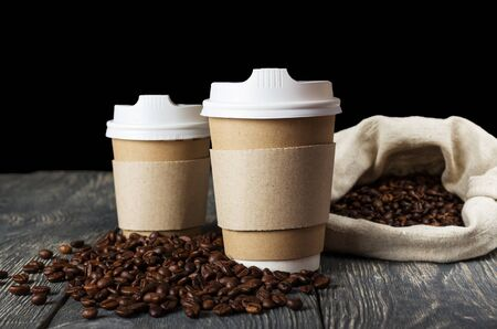 Two single-use container for hot drinks to take away, on background of scattered coffee beans