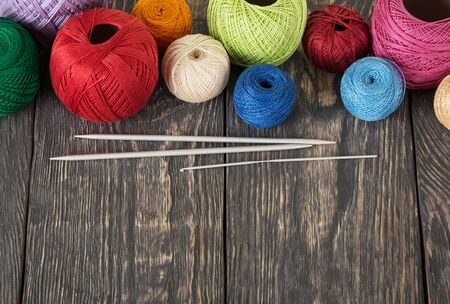 Multicolored balls of cotton threads for needlework, on dark wooden surface