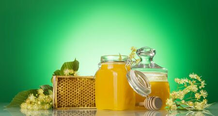 Two glass jars of honey, wooden frame with honeycomb and Linden branches, on light green background
