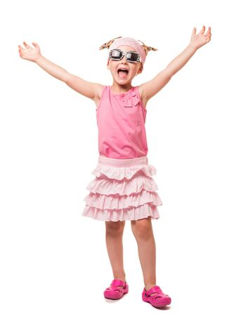 Cheerful little blonde in sunglasses with his hands raised up isolated on white background.