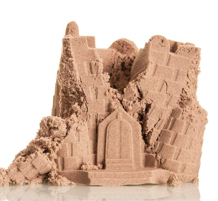 Half-ruined tower of sand isolated on a white background. Banque d'images