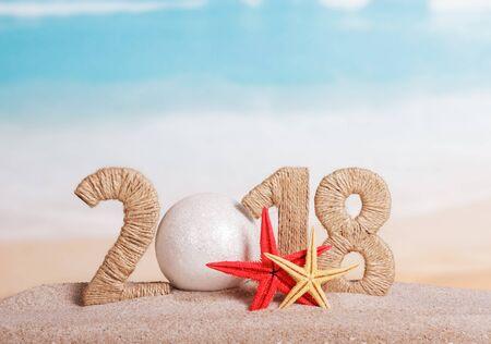 Inscription du Nouvel An 2018, au lieu du numéro - boule blanche, étoile de mer dans le sable sur la plage.