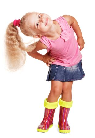 An impish little blond girl in a blouse, a skirt and rubber boots isolated on white background.