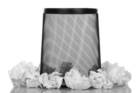 Black empty basket for paper waste bottom up and around balls of crumpled paper isolated on white background.