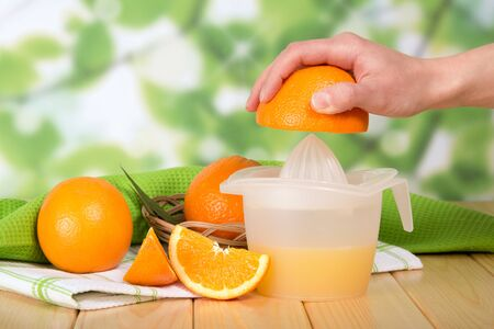 Female hand squeezes an orange by hand juicer, on wooden table Stock Photo