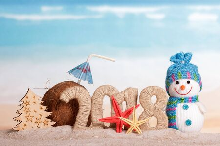 New Year inscription 2018, coconut with drinking straw and umbrella, the snowman and the Christmas tree, starfish on the sand.