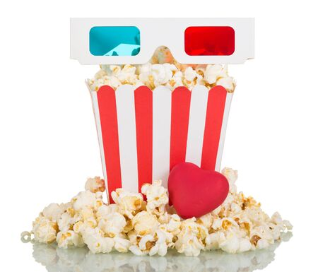 3D glasses, a large square box of popcorn, popcorn around and red heart isolated on white background.