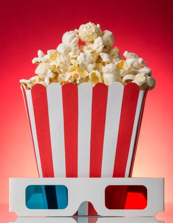 A large square box of popcorn and 3D glasses beside on a bright red background.