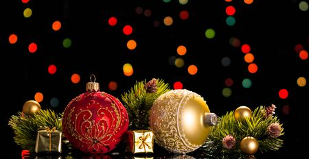 Large and small decorative balls, pine branches, small gift boxes, on a flickering background